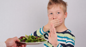 Child being offered a plate of salad greens then covering mouth with one hand and pushing away the plate with opposite hand